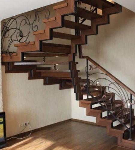 Металлокаркас лестницы с ковкой обшитая деревом наковали